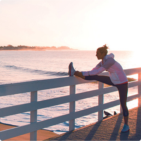Jogger stretching on a fence overlooking the ocean