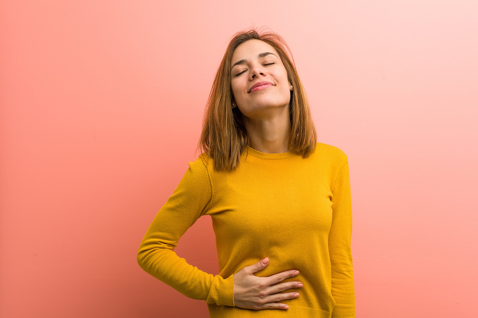 woman smiling with hand on stomach