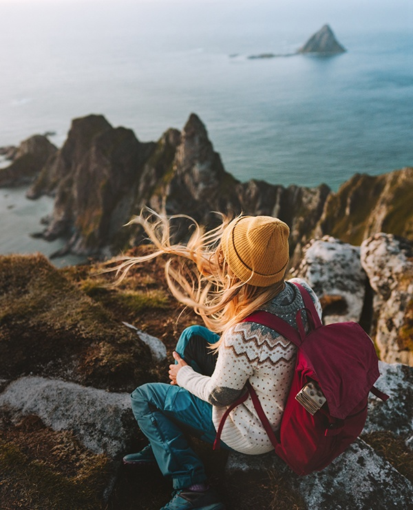 Girl hiking looking at the ocean view on rock